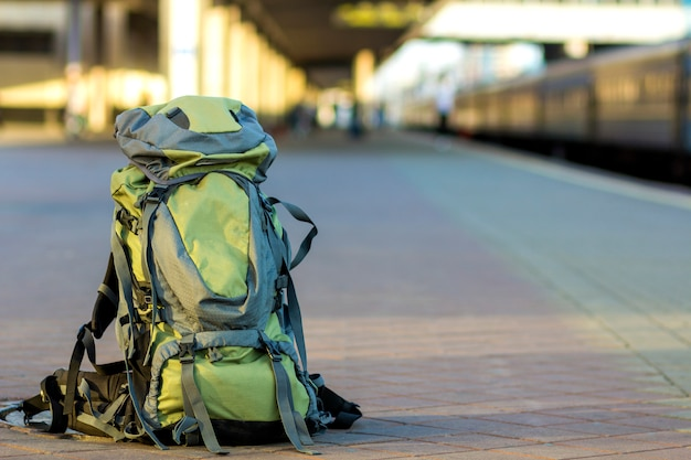 Close-up of big green tourist backpack on railway station platform. traveling, adventure and recreation concept. Premium Photo