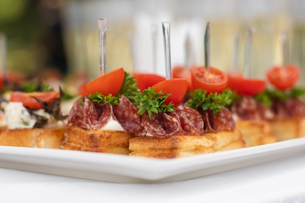 Close-up big plate with serving snack canapes fried bread tomato parsley and salami Premium Photo
