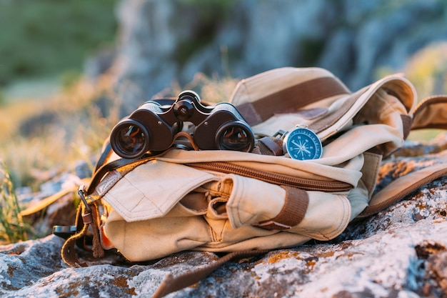 Close-up of binocular, compass and bag on rock Free Photo