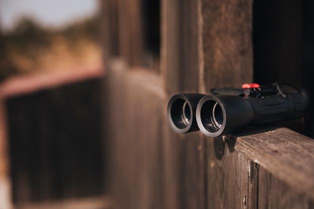 Close-up binoculars on a wooden ledge Free Photo