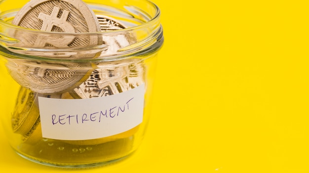 Close-up of bitcoins in the retirement glass jar on yellow background Free Photo