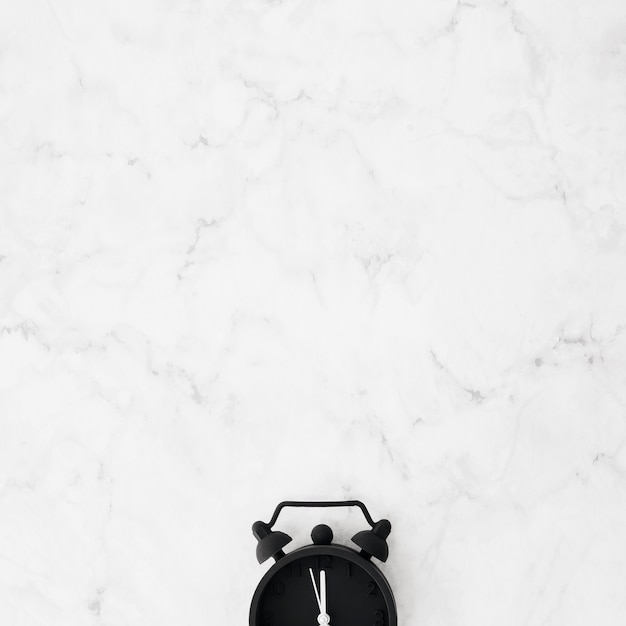 Close-up of black alarm clock over the marble textured desk Free Photo