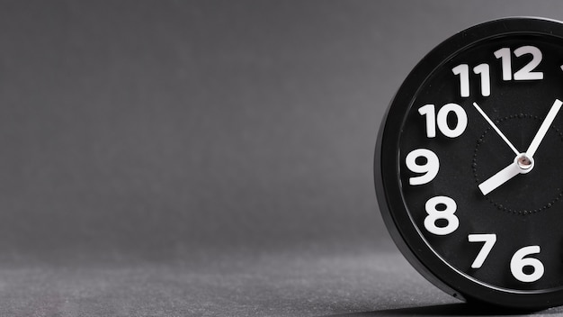 Close-up of a black clock against gray background Free Photo