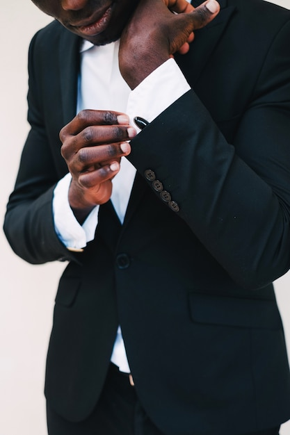 Close-up of a black man in a tuxedo fixing his cufflinks.groom bow tie cufflinks Premium Photo