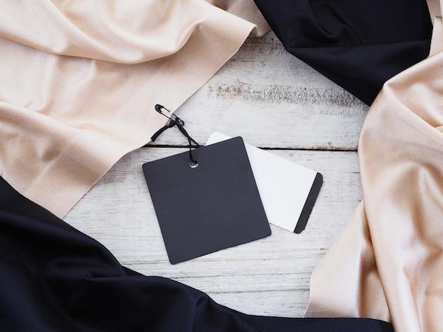 Закройте вверх по бирке продажи черной бумаги, висящей на шелковой ткани над белой винтажной деревянной предпосылкой. Premium Фотографии
