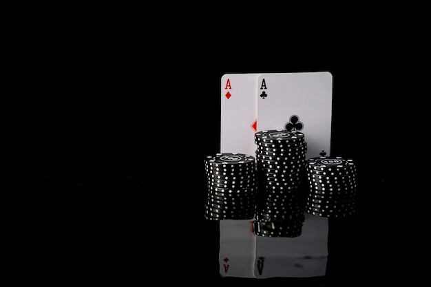 Close-up of black poker chips and two aces playing cards Free Photo