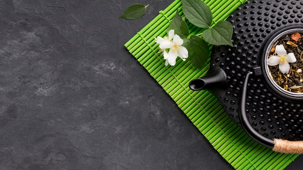 Close-up of black teapot with dried tea herb on green placemat over textured background Free Photo