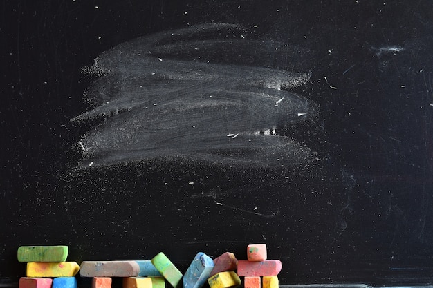 Close-up of blackboard with pieces of colored chalk Free Photo