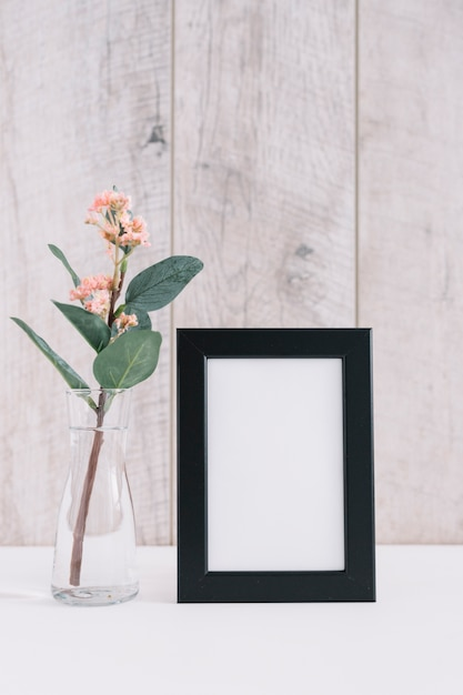 Close-up of blank picture frame with flower vase Free Photo