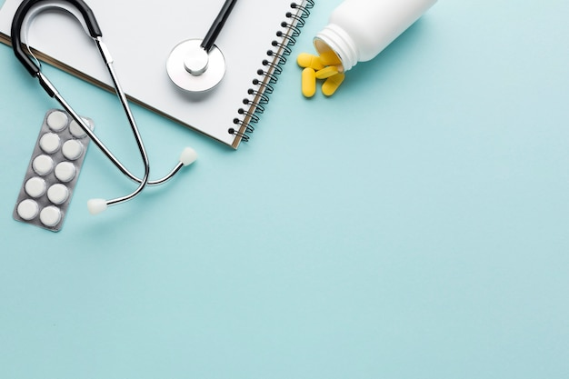 Close-up of blister packed medicine; stethoscope; spiral notepad above blue background Free Photo