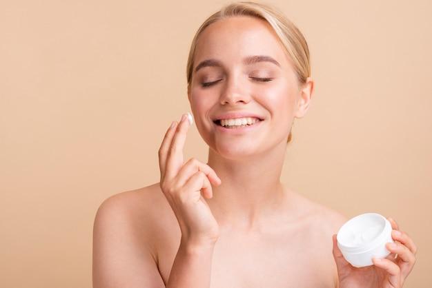 Close-up blonde model using face cream Free Photo