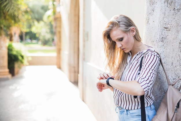 Close-up of blonde young woman checking her time on watch Free Photo