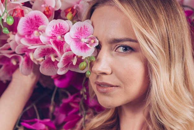Close-up of blonde young woman covering her one eyes with pink orchid Free Photo
