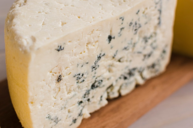 Close-up of blue cheese slice on wooden chopping board Free Photo