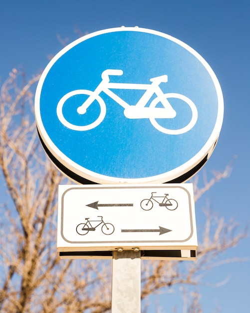 Close-up of blue cycle sign against blue sky Free Photo