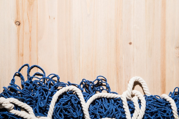 Close-up of blue fishing net with white rope on wooden surface Free Photo