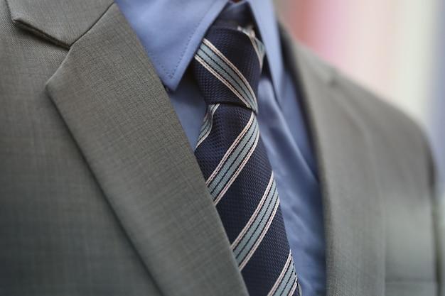 Close up blue necktie with grey suit Premium Photo