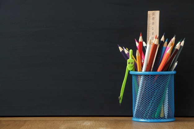 Close-up blue stand with school stationery on the background of a large black chalk board Premium Photo