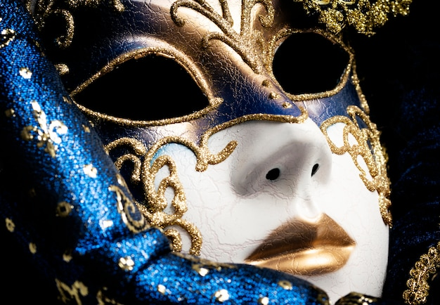 Close up of a blue with gold elegant traditional venetian mask over white background Premium Photo