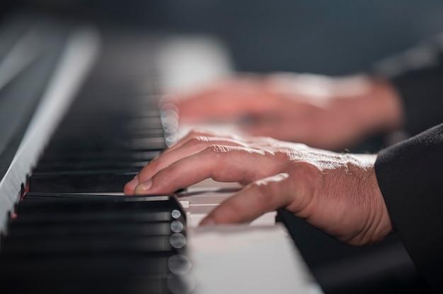 Крупным планом размытые руки, играющие на цифровом пианино Бесплатные Фотографии