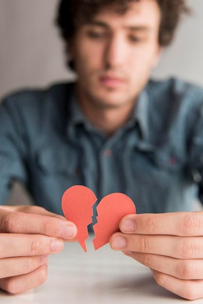 Close-up blurred man holding broken heart Premium Photo