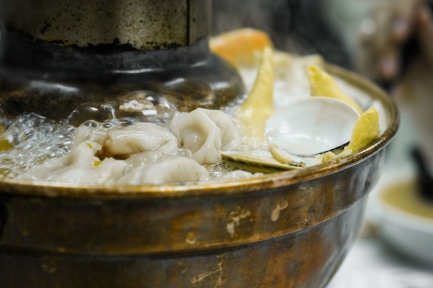Close-up boiling oysters and dumplings in pot Free Photo