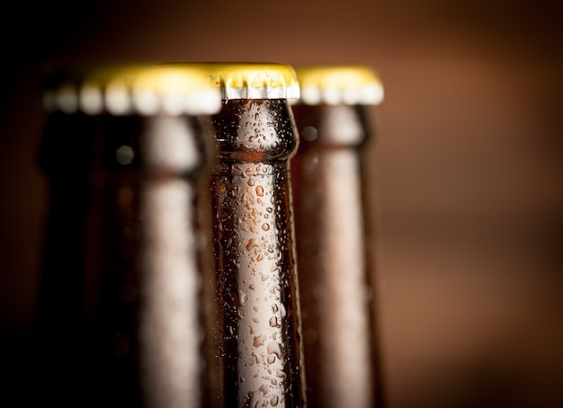 Close up bottle of beer with drops on dark background Premium Photo