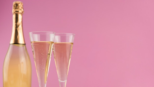 Close-up of bottle of champagne with glasses and copy space Free Photo