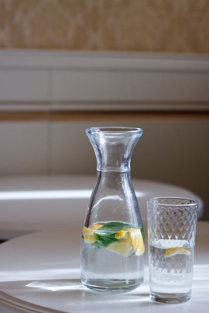 Close-up of a bottle with a cap and a glass of water with mint and lemonon a white table and sun glare Premium Photo