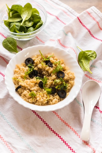 Close-up of a bowl of healthy oats garnished with basil leaf and olive for breakfast Free Photo
