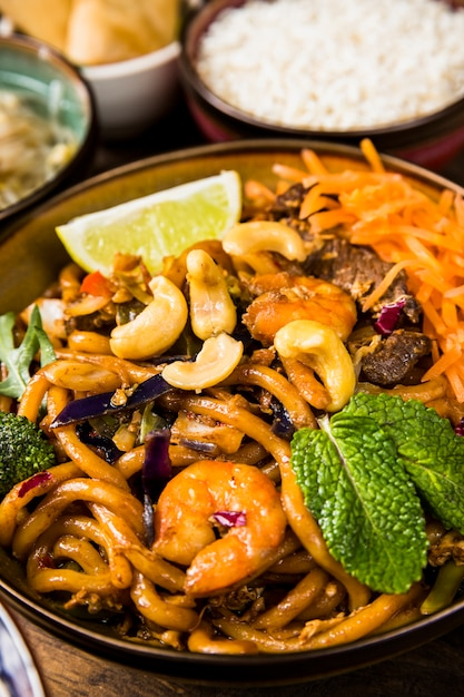 Close-up bowl of udon noodles with nuts; lemon slice; mint and beefs Free Photo