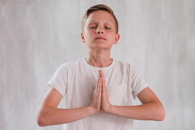 Close-up of a boy closing his eyes doing meditation against concrete wall Free Photo