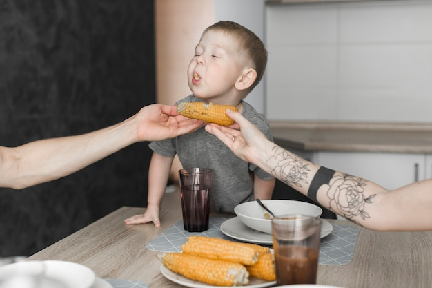 Close-up of a boy eating corn hold by her parent at breakfast Free Photo