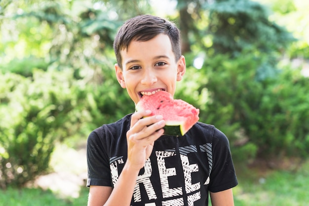 Close-up of a boy eating watermelon slice in the park Free Photo