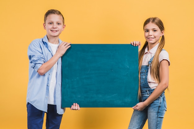 Close-up of a boy and girl holding green chalkboard against yellow backdrop Free Photo