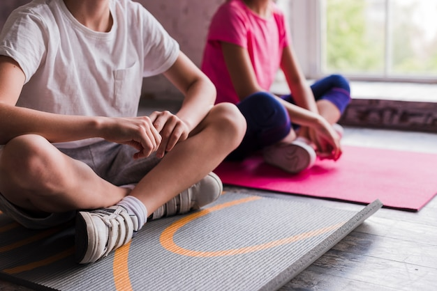 Close-up of a boy and girl sitting on grey and pink exercise mat Free Photo