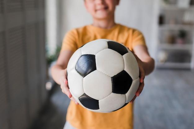 Close-up of boy giving soccer ball toward camera Free Photo