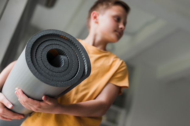 Close-up of a boy holding rolling grey exercise mat looking away Free Photo