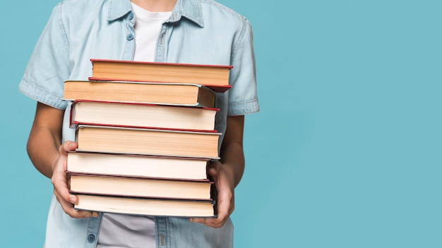 Close-up boy holding stack of books Free Photo