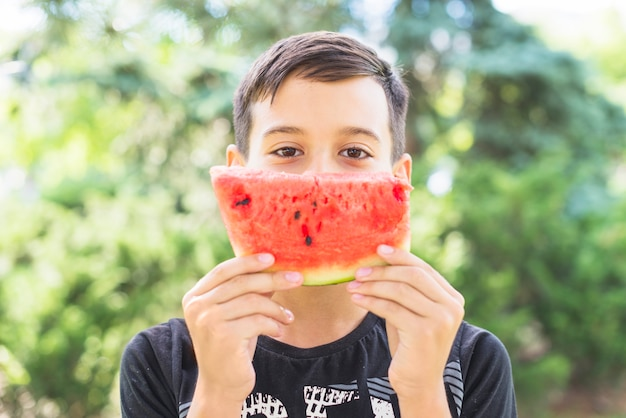 Close-up of a boy holding watermelon slice over his mouth Free Photo