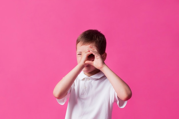 Close-up of boy looking through hand as binoculars over pink wall background Free Photo