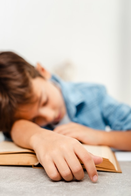 Close-up boy sleeping on book Free Photo