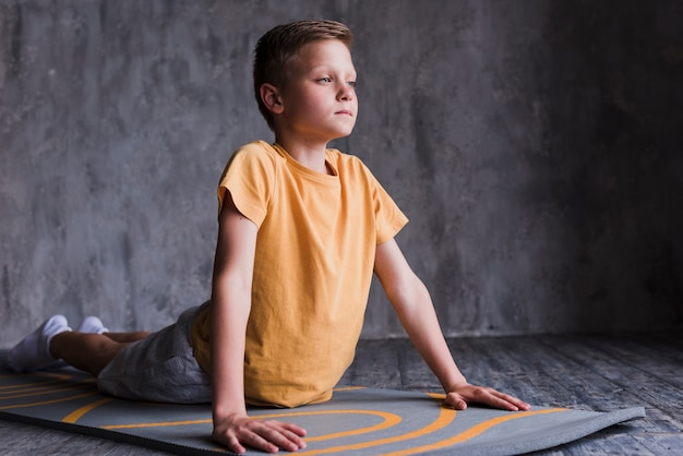 Close-up of a boy stretching on exercise mat in front of concrete wall Free Photo