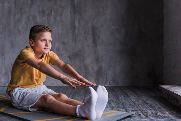 Close-up of a boy wearing white socks stretching his hand Free Photo