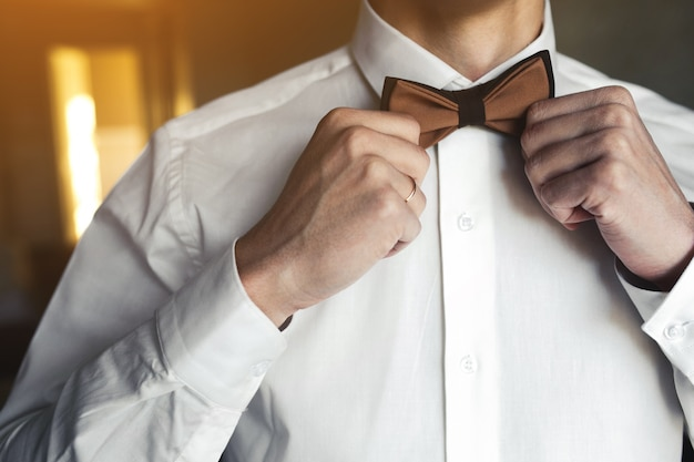 Close-up of a boyfriend arranging his bow tie Free Photo