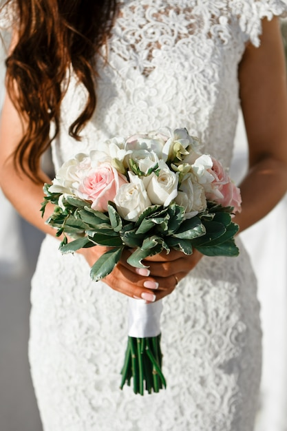 Close-up bridal bouquet of spring pink and white flowers on a blurred background, selective focus Premium Photo