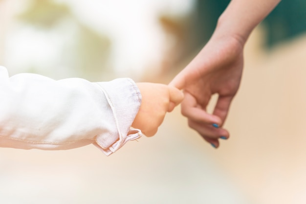 Close-up of a brother holding sister's finger Free Photo