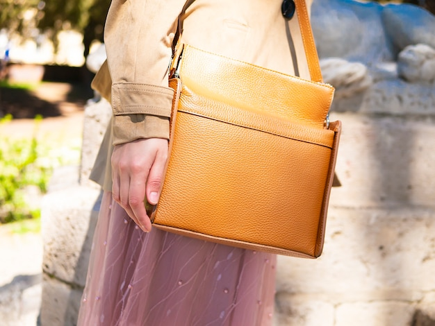 Close up of brown orange stylish bag. elegant, trendy outfit. Premium Photo