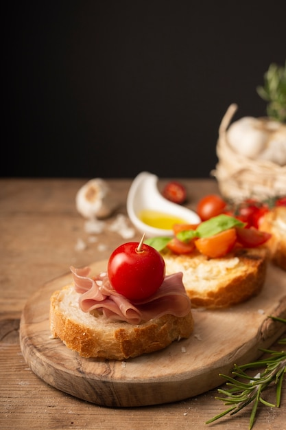 Close up bruschettas with prosciutto and tomatoes Free Photo