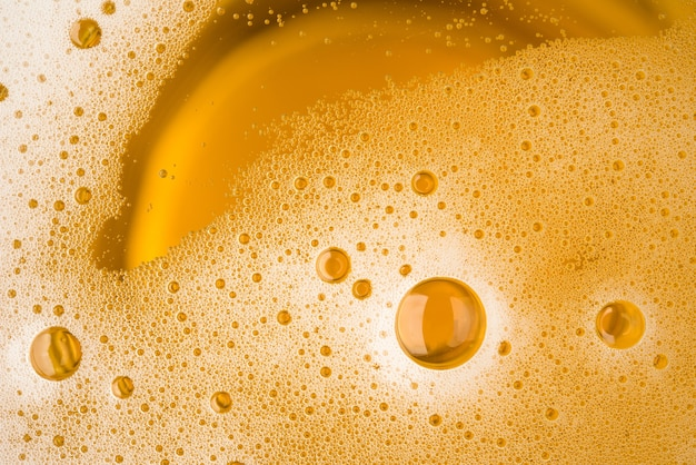 Close up bubble froth of beer in glass or mug for background on top view Premium Photo